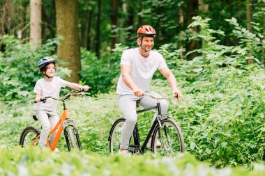 Selective focus of father and son smiling and looking forward while riding bicycles in forest stock vector