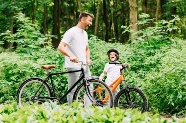 Selective focus of father and son laughing while standing with bicycles on road near forest stock vector