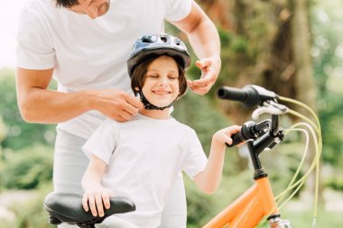 cropped view of father putting helmet on son while boy smiling and standing near bicycle