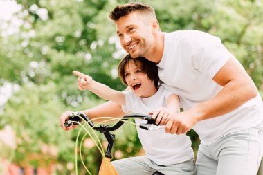 Excited father and son looking forward while boy pointing with finger and dad helping kid to ride on bicycle stock vector