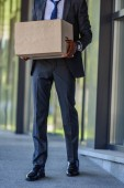 cropped view of dismissed african american businessman holding carton box