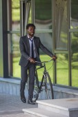 smiling african american businessman walking with bicycle near office building