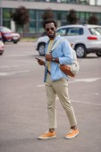 handsome african american man in sunglasses holding smartphone while standing on car parking