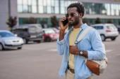 pohledný afroamerický muž, který mluví na telefonu, zatímco stojí na parkovišti a dívá se jinam