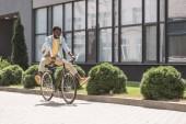 Veselý, elegantní afroamerický muž usměvavý při jízdě na kole
