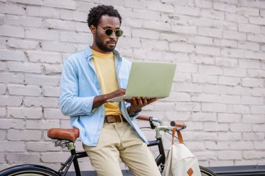 Attentive, stylish african american man using laptop while standing by brick wall near bicycle stock vector