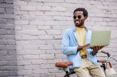 Smiling african american man looking away while standing by brick wall near bicycle and using laptop stock vector