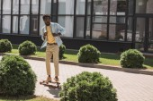 handsome african american man longboarding on sunny street near building and green bushes