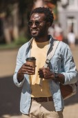 Stylový, veselý africký Američan, který se dívá stranou a současně drží na sobě pohár