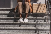 cropped view of dismissed african american businessman sitting on stairs near carton box