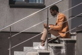 side view of stylish african american businessman sitting on stairs and using laptop