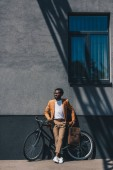 handsome, stylish african american businessman standing with bicycle near wall