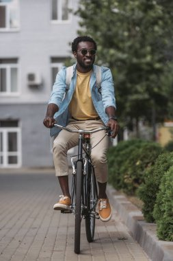 cheerful, stylish african american man smiling while riding bicycle