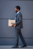 side view of fired african american businessman holding carton box while walking on street