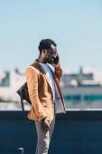 Stylový afroamerický obchodník mluvící na telefonu a s úsměvem na střeše