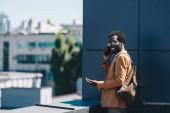 Fotografia allegro uomo daffari africano americano parlare sullo smartphone e sorridere mentre in piedi sul tetto