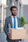 dismissed, upset african american businessman holding carton box and looking at camera