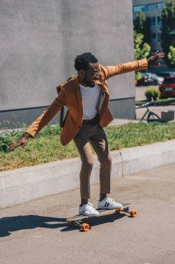 Cheerful african american businessman riding longboard on sunny street stock vector
