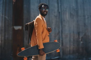 Stylish african american businessman holding longboard and smiling at camera stock vector