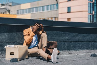 upset african american businessman holding hands near head while sitting on rooftop near carton box