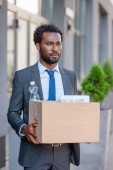 dismissed african american businessman looking away while holding carton box