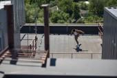 szelektív középpontjában az afroamerikai üzletember longboarding a napfényes tetőtéri