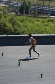 stylish african american businessman riding longboard on sunny rooftop