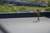 Fotografie selektivní zaměření afrického amerického podnikatele na jízdu na dlouhé terase na slunné střeše s železnicemi a vlaky na pozadí