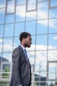 magabiztos afro-amerikai üzletember öltöny séta épület üveg homlokzata