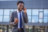 šťastný Afričan, americký podnikatel zobrazující Ano gesto při mluvení na smartphone