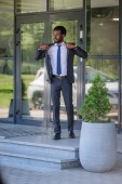 handsome african american businessman in suit looking away while standing near office building