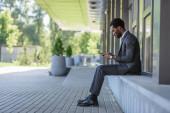 gondolkodó afro-amerikai üzletember segítségével okostelefon ülve mellvéd