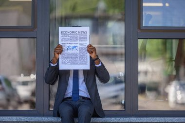 african american businessman reading economic news newspaper while sitting near office building with glass facade