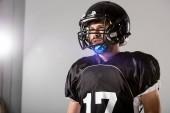 Americký fotbalový hráč v helmici na šedé se zadní osvětlenou a kopírovací mezerou