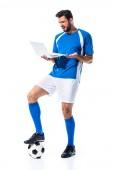 zavaros futballista laptop és állva a labdát izolált fehér