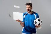 Aufgeregter Fußballer mit Ball und Laptop vor fallendem Geld auf grau