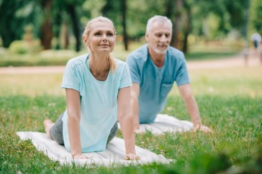 smiling man and woman practicing relaxation yoga poses on yoga mats