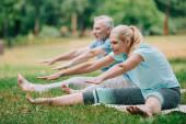 lächelnde reife Männer und Frauen üben Dehnpositionen, während sie im Park auf Yogamatten sitzen