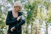 vonzó, érett sportoló hallgató zene fülhallgató a parkban