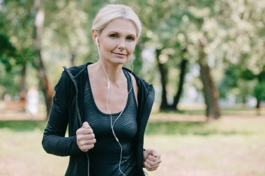 beautiful mature sportswoman smiling at camera while running in park and listening music in earphones