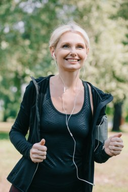 cheerful mature sportswoman jogging in park and listening music in earphones