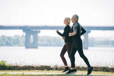 mature sportsman and sportswoman running along riverside in park