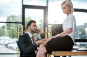 handsome man touching leg of attractive girl sitting on table