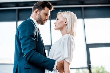 low angle view of bearded man looking at blonde girl while flirting in office