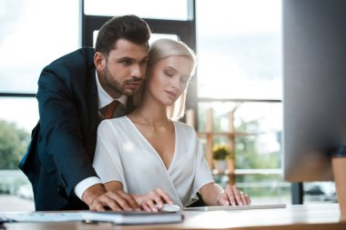 selective focus of bearded businessman in suit standing near attractive blonde girl in office
