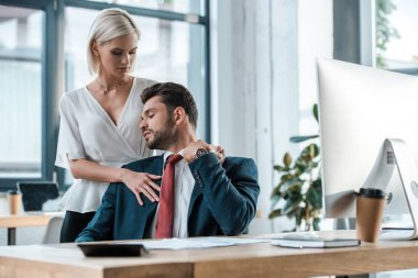 selective focus of blonde woman standing and flirting with businessman in office