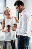 attractive blonde woman in glasses looking at upset coworker while holding paper cup