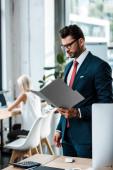 selektivní zaměření hezkého obchodníka na brýle se zaměřením na složku u spolupracovníka