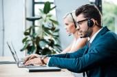 selektivní zaměření pohledného muže v náhlavní soupravě psaní na přenosný počítač při práci v blízkosti kolegy