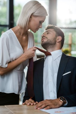 passionate woman touching tie of handsome man while flirting in office